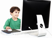 Menino novo com computador de secretária Fotografia de Stock