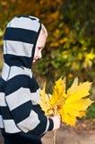 Menino novo com folhas amarelas fotos de stock royalty free