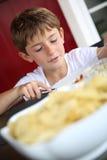 Menino novo com fome que come o alimento grelhado Fotografia de Stock