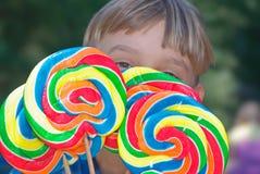 menino novo com lollipops Fotografia de Stock Royalty Free