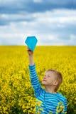 Menino novo com o avião de papel contra o céu azul foto de stock royalty free