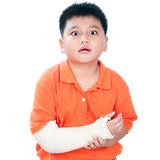 Menino novo com o braço quebrado no molde de emplastro foto de stock