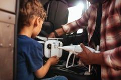 Menino novo com o pai que guarda o zangão pequeno na viagem por estrada imagens de stock