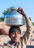Menino novo com o potenciômetro do metal da água em sua cabeça Fotografia de Stock Royalty Free