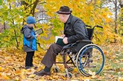 Menino novo com o seu avô deficiente fotografia de stock royalty free