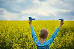 Menino novo com plano de papel contra o céu azul e o campo amarelo Flo fotos de stock