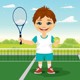 Menino novo com raquete e bola no sorriso do campo de tênis Fotografia de Stock Royalty Free
