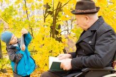 Menino novo com seu avô em uma floresta do outono fotos de stock