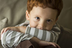 Menino novo com seu queixo em seus braços Foto de Stock