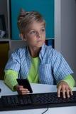 Menino novo com telefone e computador Fotografia de Stock