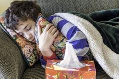 Menino novo com uma gripe fria que encontra-se para baixo dormindo no sofá e no huggi foto de stock