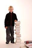 Menino novo com uma pilha dos livros Foto de Stock