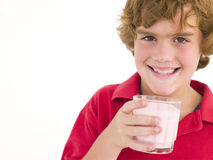 Menino novo com vidro do sorriso do leite Fotos de Stock