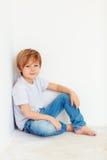 Menino novo considerável, criança que senta-se perto da parede branca imagens de stock
