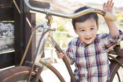 Menino novo da raça misturada que tem o divertimento na bicicleta fotos de stock