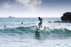 Menino novo da silhueta que surfa em ondas Fotografia de Stock Royalty Free