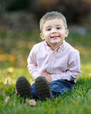Menino novo de sorriso na grama Imagens de Stock Royalty Free