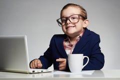 Menino novo do negócio criança de sorriso nos vidros chefe pequeno no escritório
