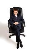 Menino novo do negócio em uma cadeira fotografia de stock royalty free