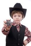 Menino novo do xerife que prende um emblema dos marechais Foto de Stock Royalty Free