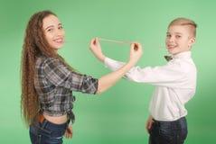 Menino novo e menina que esticam da pastilha elástica que leva dentro sua boca Fotografia de Stock Royalty Free