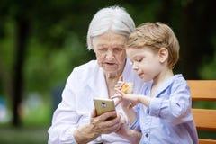 Menino novo e sua bisavó que usa o smartphone fora Fotos de Stock Royalty Free