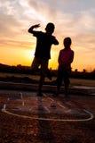 Menino novo e uma menina que joga amarelinha no por do sol Imagens de Stock Royalty Free
