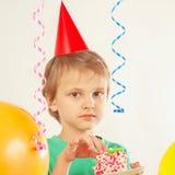 Menino novo em um chapéu do feriado que come a parte de bolo de aniversário Imagens de Stock
