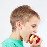 Menino novo em uma camisa verde que come a maçã vermelha Fotos de Stock Royalty Free