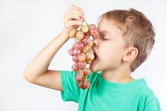 Menino novo em uma camisa verde que come a uva Fotografia de Stock