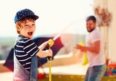 Menino novo entusiasmado que tem o divertimento, espirrando a água com o pai no dia de verão morno Foto de Stock