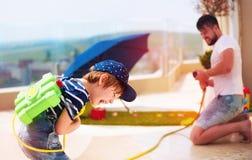 Menino novo entusiasmado que tem o divertimento, espirrando a água com o pai no dia de verão morno Foto de Stock Royalty Free