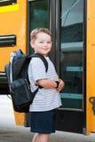 Menino novo feliz na frente do auto escolar Imagens de Stock