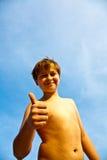 Menino novo feliz na praia com polegares acima Fotografia de Stock
