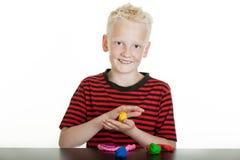 Menino novo feliz que joga com argila de modelagem Imagem de Stock