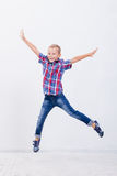 Menino novo feliz que salta no fundo branco Foto de Stock Royalty Free
