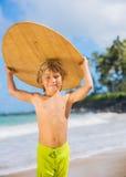 Menino novo feliz que tem o divertimento na praia em férias imagem de stock