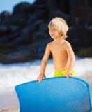 Menino novo feliz que tem o divertimento na praia em férias, fotos de stock