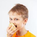 Menino novo na camisa alaranjada que come uma pera amarela suculenta Fotografia de Stock Royalty Free