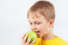 Menino novo na camisa amarela com maçã verde imagens de stock royalty free