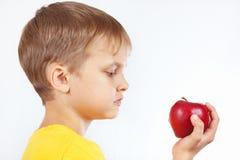 Menino novo na camisa amarela com maçã vermelha Imagem de Stock Royalty Free