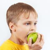 Menino novo na camisa amarela que come uma maçã verde fotos de stock