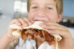 Menino novo na cozinha que come o sanduíche do bacon Foto de Stock Royalty Free