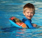 Menino novo na piscina com um anel de borracha fotos de stock