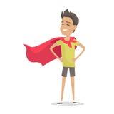 Menino novo na pose do superman que veste um casaco vermelho Fotos de Stock Royalty Free