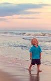 Menino novo na praia no por do sol Imagem de Stock