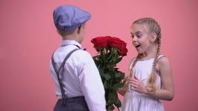 Menino novo na roupa formal que esconde rosas atrás da parte traseira e que apresenta à menina vídeos de arquivo