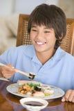 Menino novo na sala de jantar que come o alimento chinês Foto de Stock Royalty Free