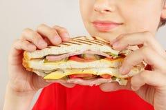 Menino novo no vermelho com um sanduíche dobro saboroso no fim branco do fundo acima fotografia de stock