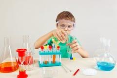 Menino novo nos óculos de proteção de segurança que fazem experiências químicas no laboratório Fotos de Stock Royalty Free